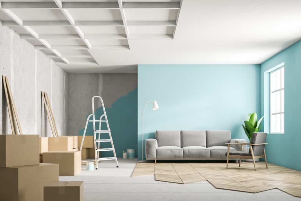 a living room with partially painted walls and half-completed floors, in the middle of renovation