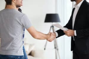 man in gray shirt shakes hands with landlord in suit holding paper