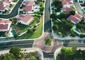 a neighborhood of red-roofed suburban homes shown from above shows the state of the real estate market