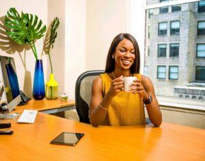 female property manager sits behind desk smiling